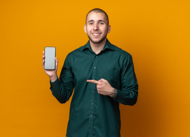 Souriant jeune beau mec vêtu d'une chemise verte tenant et pointe au téléphone