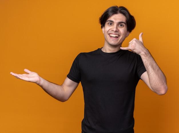 Souriant jeune beau mec vêtu d'un t-shirt noir montrant un geste d'appel téléphonique écartant la main isolée sur un mur orange avec espace de copie