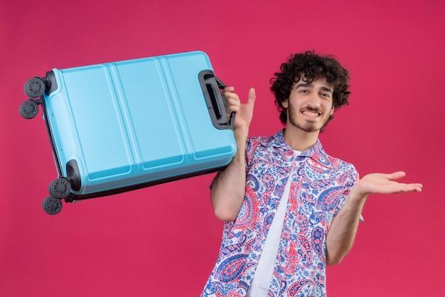 Souriant jeune beau voyageur bouclé homme tenant valise montrant la main vide sur un mur rose isolé