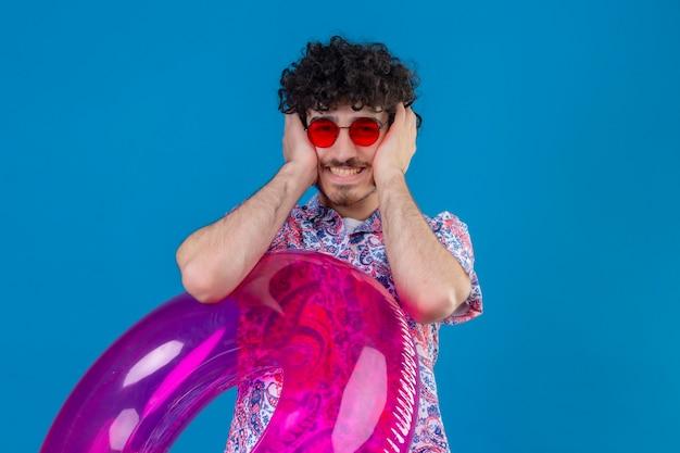 Souriant jeune bel homme bouclé portant des lunettes de soleil tenant un anneau de bain mettant les mains sur les oreilles sur un mur bleu isolé avec espace de copie