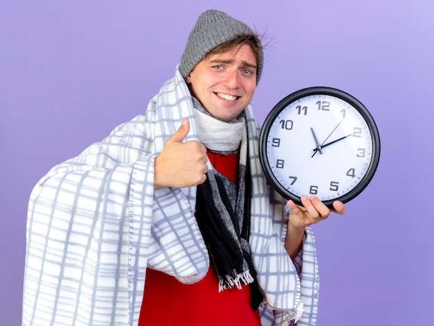 Souriant jeune bel homme malade blonde portant un chapeau d'hiver et une écharpe enveloppée dans un plaid tenant une horloge regardant la caméra montrant le pouce vers le haut isolé sur fond violet
