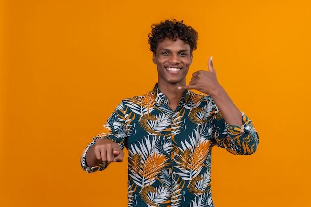 Souriant jeune bel homme à la peau sombre avec des cheveux bouclés en chemise imprimée de feuilles faisant un appel-moi signe avec sa main tout en pointant avec l'index sur un fond orange