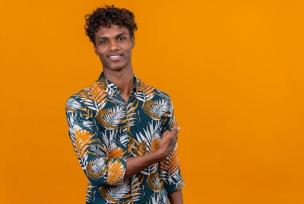 Souriant jeune bel homme à la peau sombre avec des cheveux bouclés en chemise imprimée de feuilles montrant quelque chose avec la main sur un fond orange