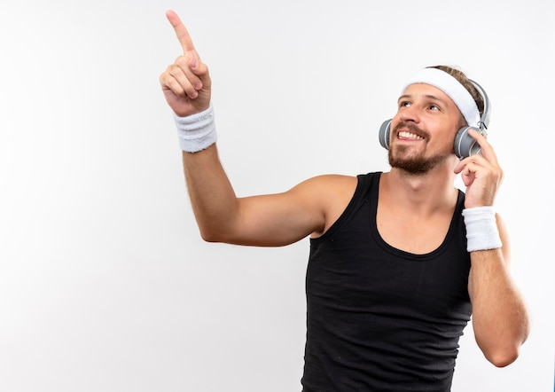 Souriant jeune bel homme sportif portant un bandeau et des bracelets et des écouteurs à la recherche et pointant vers le haut avec une main sur le casque isolé sur un espace blanc