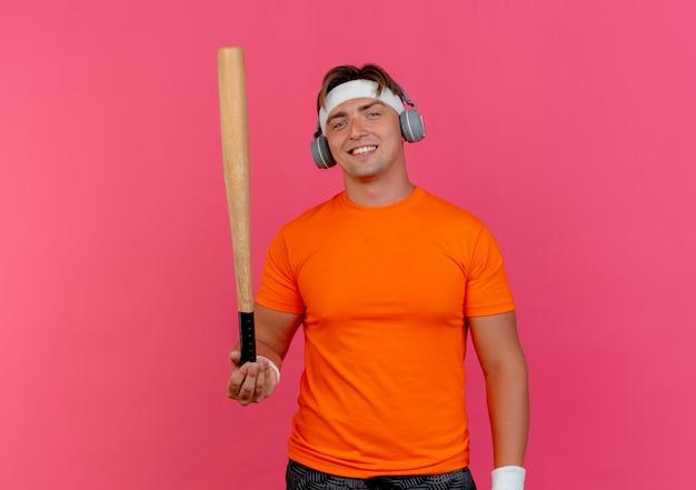 Souriant jeune bel homme sportif portant un bandeau et des bracelets et des écouteurs tenant une batte de baseball isolé sur un mur rose