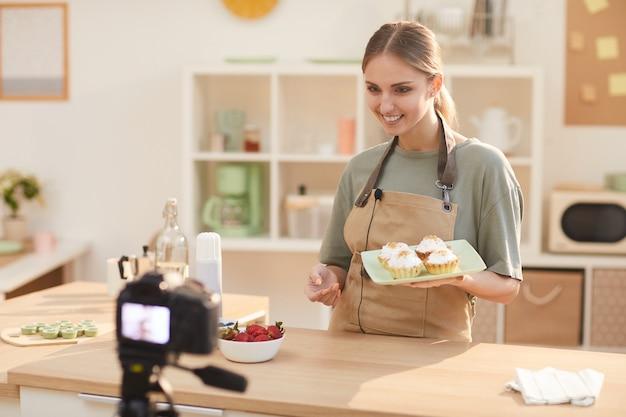 Souriant jeune blogueur alimentaire tenant des gâteaux cuits au four sur l'assiette et les montrant à la caméra pendant la prise de vue du contenu