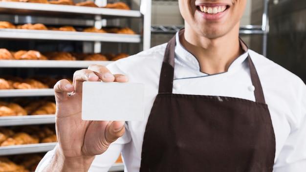 Souriant jeune boulanger mâle tenant la carte de visite blanche vierge