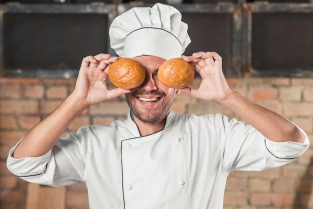 Souriant jeune boulanger mâle tenant chignon sur les yeux
