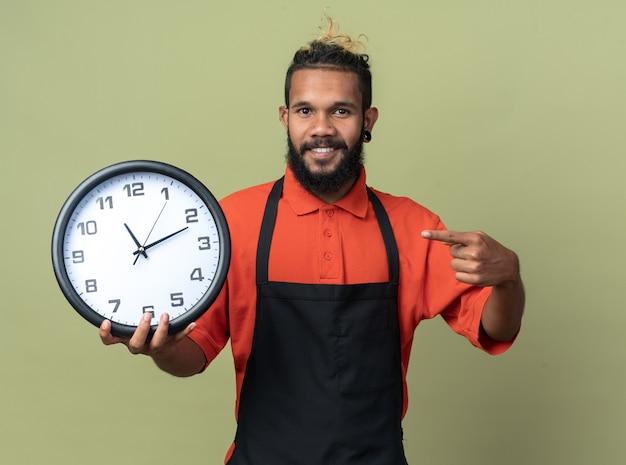Souriant jeune coiffeur afro-américain en uniforme tenant pointant sur l'horloge