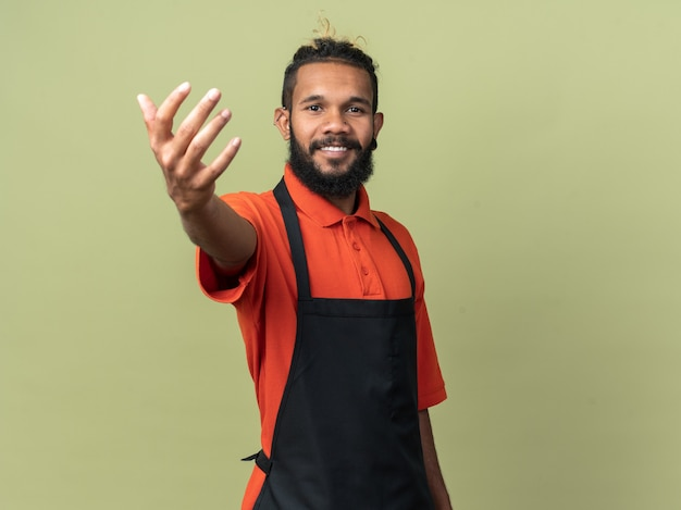 Souriant jeune coiffeur afro-américain en uniforme tendant la main vers