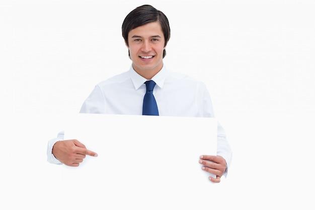 Souriant jeune commerçant pointant sur signe vierge dans ses mains