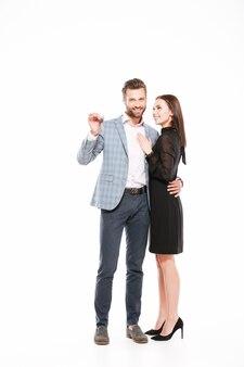Souriant jeune couple d'amoureux debout isolé tenant les clés.