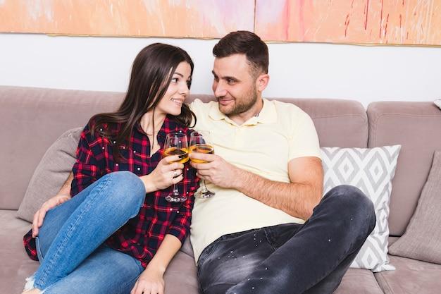 Souriant jeune couple assis sur un canapé tenant des boissons à la main