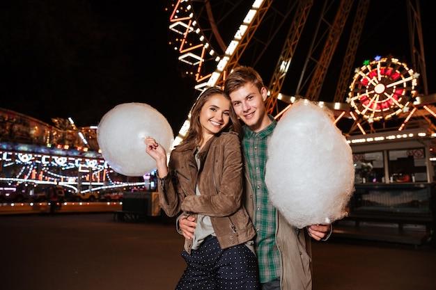 Souriant jeune couple avec barbe à papa. dans un parc d'attractions.