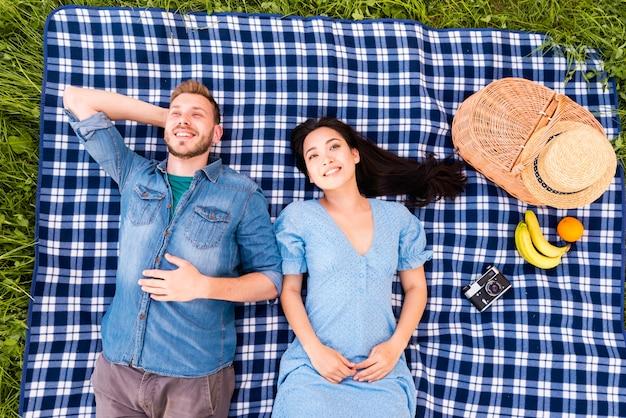 Souriant jeune couple couché sur l'herbe