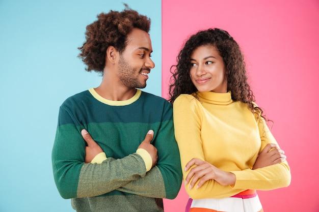 Souriant jeune couple debout avec les mains jointes et se regardant