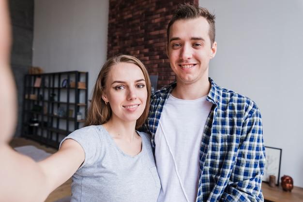 Souriant jeune couple faisant selfie à la maison
