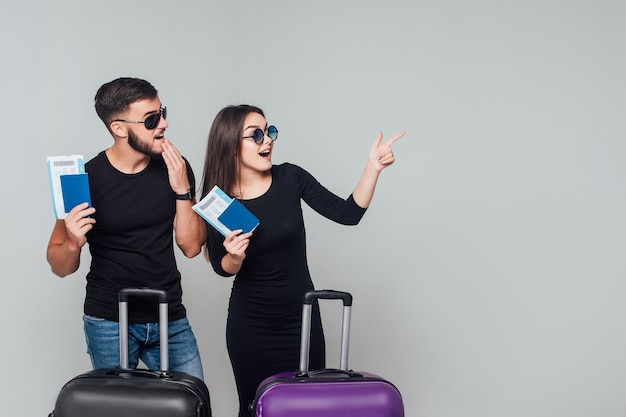 Souriant jeune couple heureux avec valises et billet autour isolé sur blanc