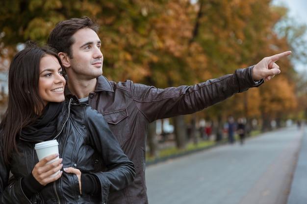 Souriant jeune couple marchant dans le parc automne et en détournant les yeux sur quelque chose
