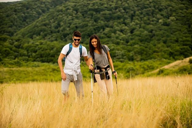 Souriant jeune couple marchant avec des sacs à dos sur les collines verdoyantes