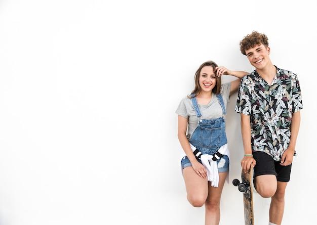 Souriant jeune couple avec planche à roulettes sur fond blanc