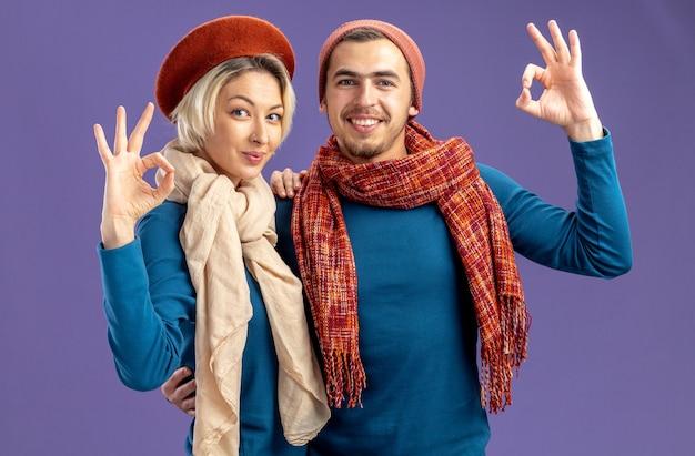Souriant jeune couple portant un chapeau avec une écharpe le jour de la saint-valentin montrant un geste correct isolé sur fond bleu