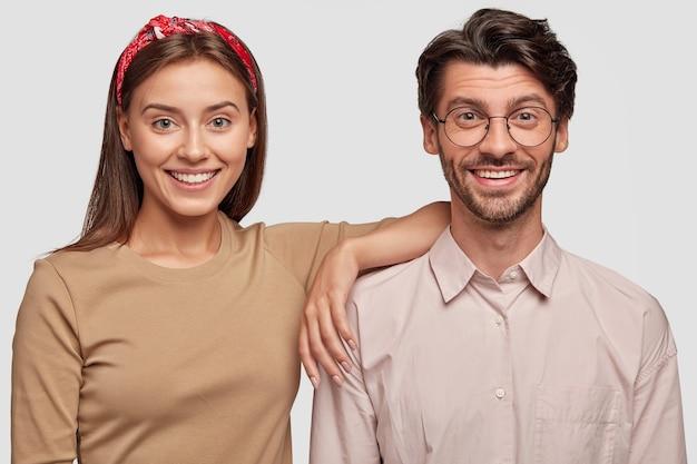 Souriant jeune couple posant contre le mur blanc