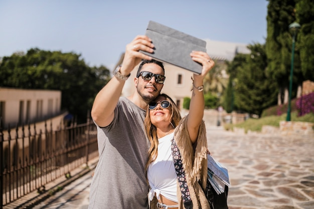 Souriant jeune couple prenant autoportrait sur tablette numérique
