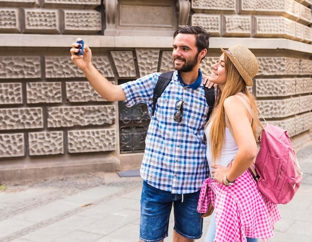 Souriant jeune couple prenant selfie sur téléphone mobile