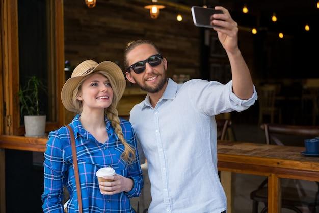 Souriant jeune couple prenant selfie avec téléphone portable dans un café
