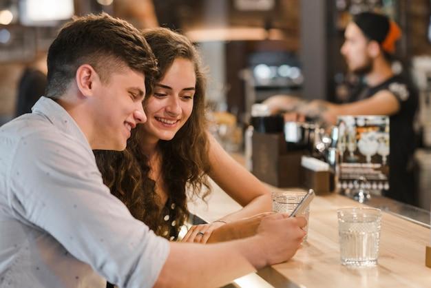 Souriant jeune couple regardant téléphone mobile près du bar comptoir