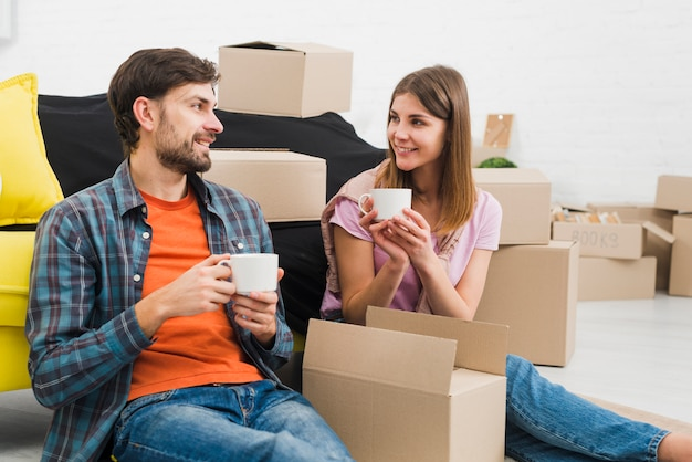 Souriant jeune couple tenant une tasse de café en regardant les uns les autres avec des boîtes en carton