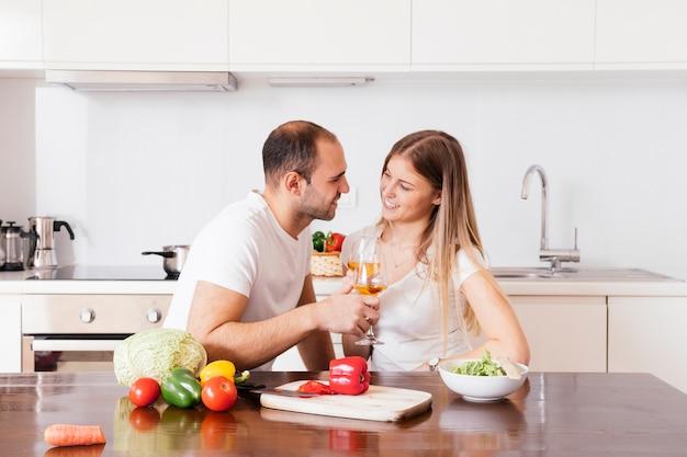 Souriant jeune couple tenant des verres de vin en regardant les uns les autres