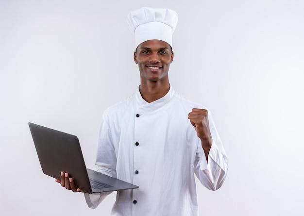 Souriant jeune cuisinier afro-américain en uniforme de chef tient un ordinateur portable et garde le poing sur fond blanc isolé avec copie espace