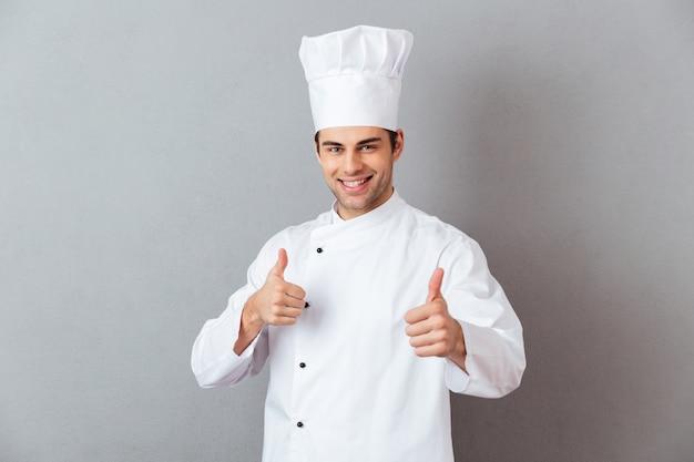 Souriant jeune cuisinier émotionnel avec les pouces vers le haut.