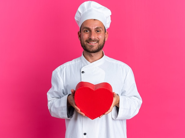 Souriant jeune cuisinier masculin de race blanche en uniforme de chef et casquette tenant en forme de coeur