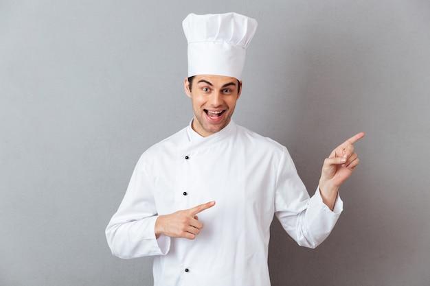 Souriant jeune cuisinier en uniforme pointant.
