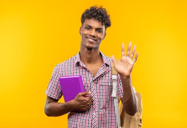 Souriant jeune étudiant afro-américain avec sac à dos tenant un livre et gardant sa main ouverte isolée sur un mur orange avec espace de copie