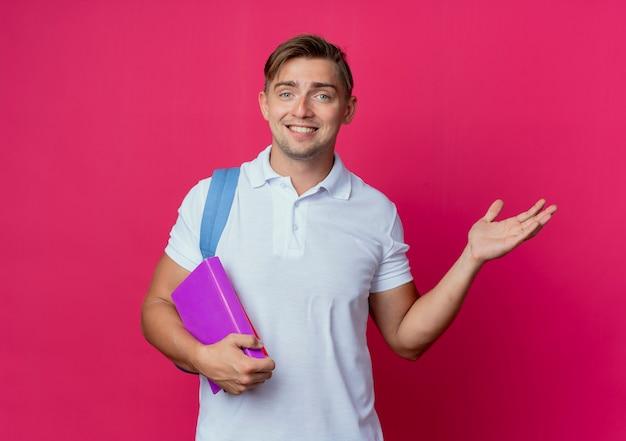 Souriant jeune étudiant beau mâle portant un sac à dos tenant des livres et des points avec main à côté isolé sur mur rose