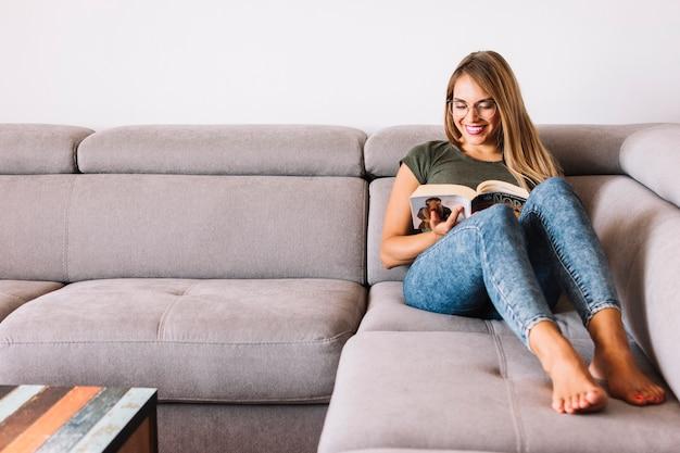 Souriant jeune femme assise sur un canapé en lisant un livre
