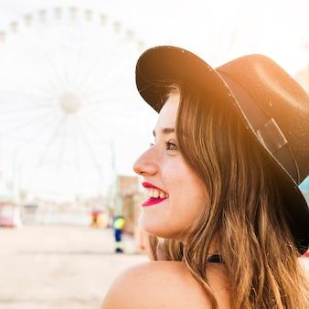 Souriant jeune femme avec un chapeau noir sur la tête