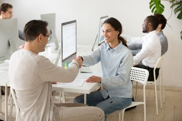 Souriant jeune femme handshaking client satisfait faisant affaire au bureau