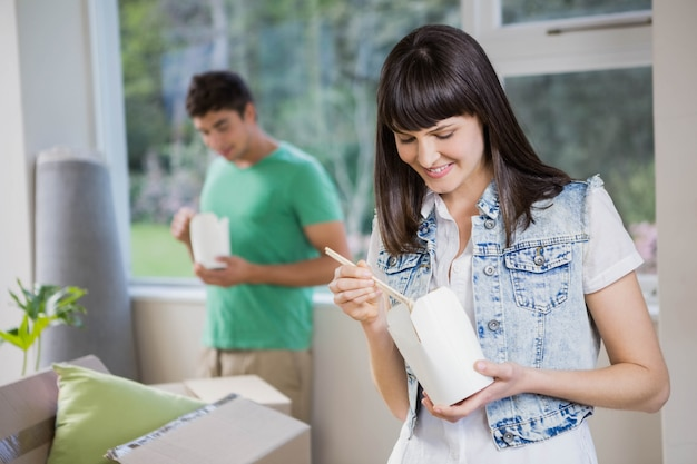Souriant jeune femme et homme mangeant des nouilles à la maison