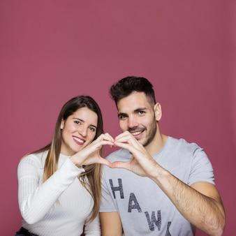Souriant jeune femme et homme montrant le coeur par des mains