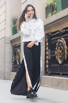 Souriant jeune femme mannequin marchant sur le trottoir parlant au téléphone mobile