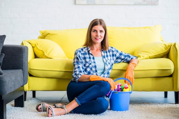 Souriant jeune femme de ménage assis sur un tapis avec du matériel de nettoyage