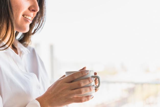 Souriant jeune femme tenant une tasse de café blanche