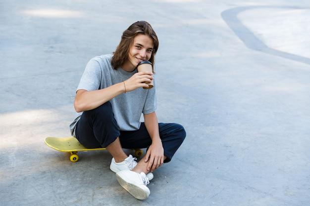 Souriant jeune garçon adolescent, passer du temps au skate park, assis sur une planche à roulettes, boire du café à emporter