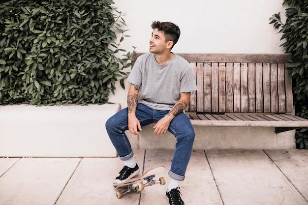 Souriant jeune garçon assis sur un banc avec longboard
