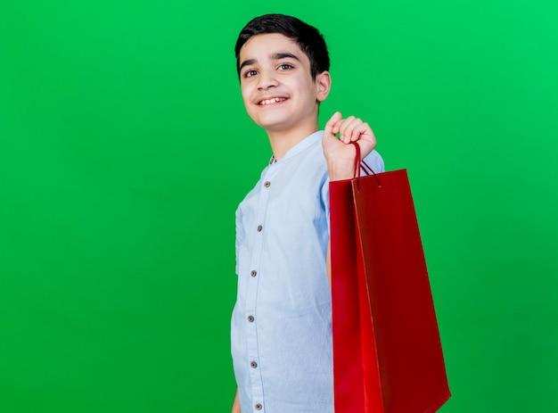 Souriant jeune garçon caucasien debout en vue de profil tenant un sac à provisions en regardant la caméra isolée sur fond vert avec espace de copie